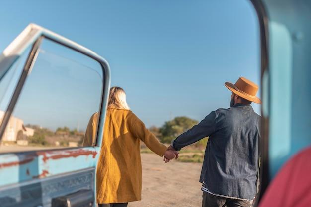 Casal jovem caminhando perto do carro e de mãos dadas