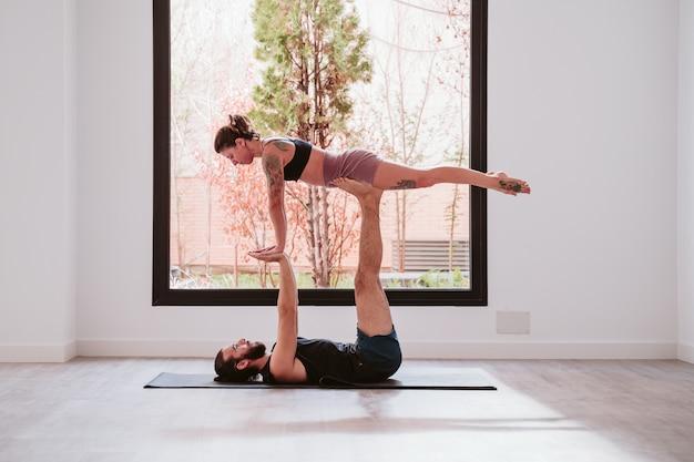 Casal jovem casal praticando acro yoga pela janela no estúdio ou no ginásio. estilo de vida saudável