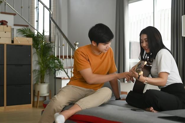 Casal jovem casual tocando violão juntos no sofá em casa.