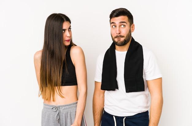 Casal jovem caucasiano fitness confuso, sente-se duvidoso e inseguro.