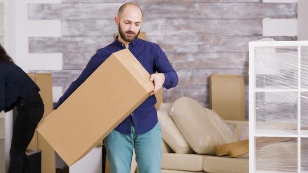 Casal jovem caucasiano se movendo em sua nova casa. movimentadores profissionais entregando caixas de papelão à porta.