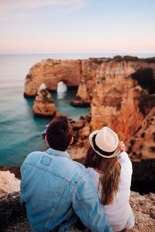 Casal jovem caucasiano sentado numa rocha admirando a bela vista do oceano e do mar e as rochas ao nascer e pôr do sol no algarve, portugal. copie o espaço.