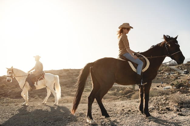 Casal jovem cavalgando fazendo excursão no campo durante o pôr do sol - foco na mulher
