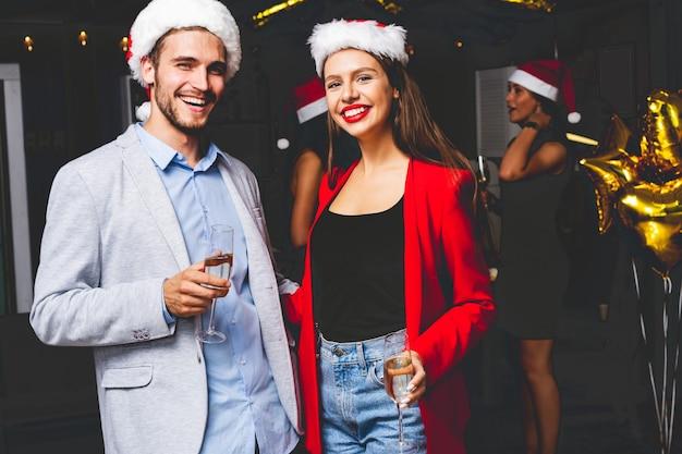 Casal jovem celebrando a véspera de ano novo com champanhe