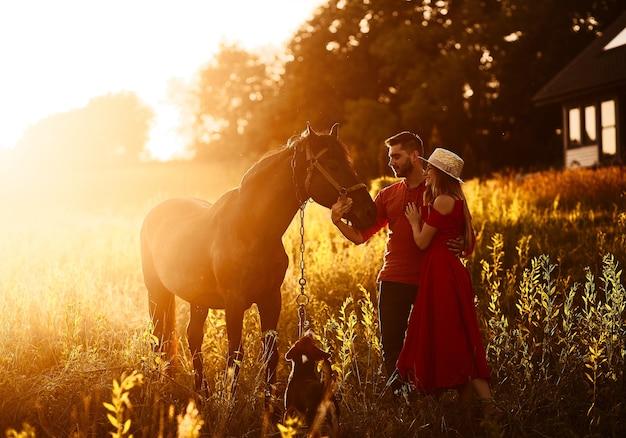 Casal jovem charmoso fica com um cavalo marrom antes de uma casa de campo
