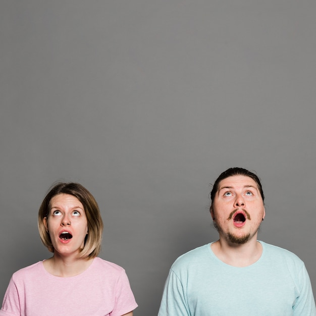 Casal jovem chocado com a boca aberta olhando contra parede cinza