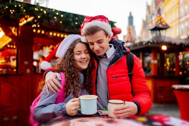 Casal jovem com bebidas no mercado de natal em wroclaw, polônia