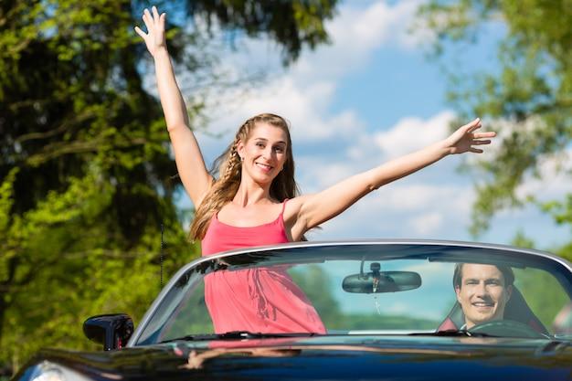Casal jovem com cabriolet no verão em viagem de um dia