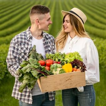 Casal jovem com cesta de legumes
