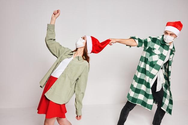 Casal jovem com chapéus de natal e emoções de férias divertidas juntos