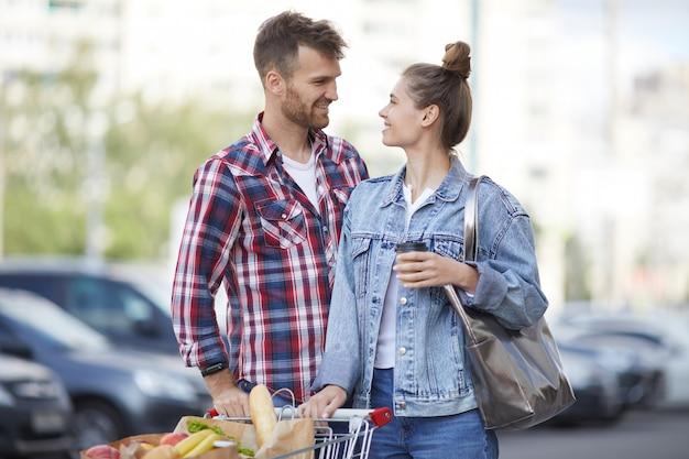 Casal jovem com compras no estacionamento