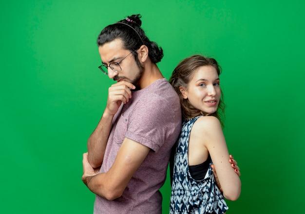 Casal jovem com expressão pensativa e mulher sorrindo em pé de costas um para o outro sobre fundo verde