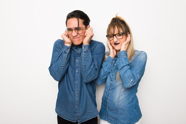Casal jovem com óculos cobrindo as orelhas com as mãos.