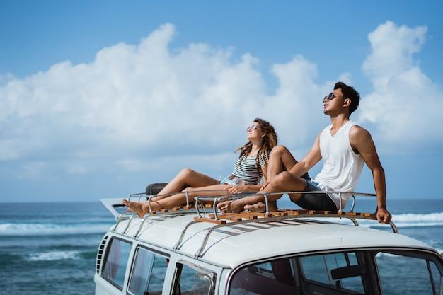 Casal jovem com óculos de sol, sentado em cima do telhado da minivan