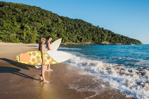 Casal jovem com pranchas de surfe