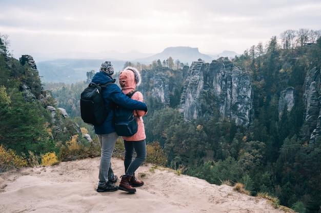 Casal jovem com roupas para atividades ao ar livre e mochilas em pé no planalto apreciando a vista do cume da montanha