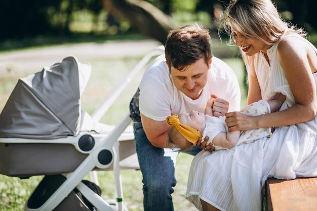 Casal jovem com sua filha bebê no parque sentado por carrinho de bebê ther