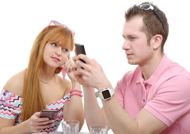 Casal jovem com telefones em branco
