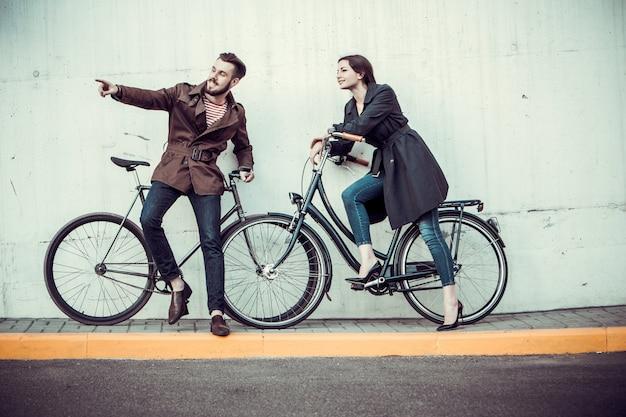 Casal jovem com uma bicicleta em frente à cidade