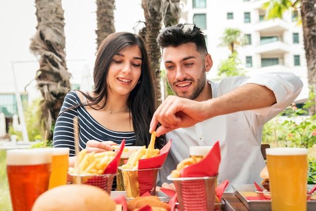 Casal jovem comendo batata frita crocante ou batata frita em uma mesa ao ar livre em um restaurante ou bar em uma cidade acompanhado de copos de cerveja gelada