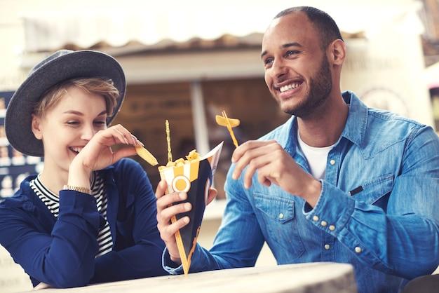 Casal jovem compartilhando batatas fritas