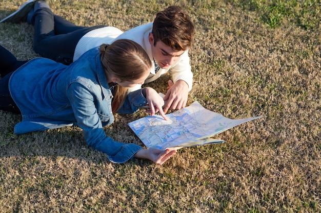 Casal jovem conferir o mapa deitada na grama
