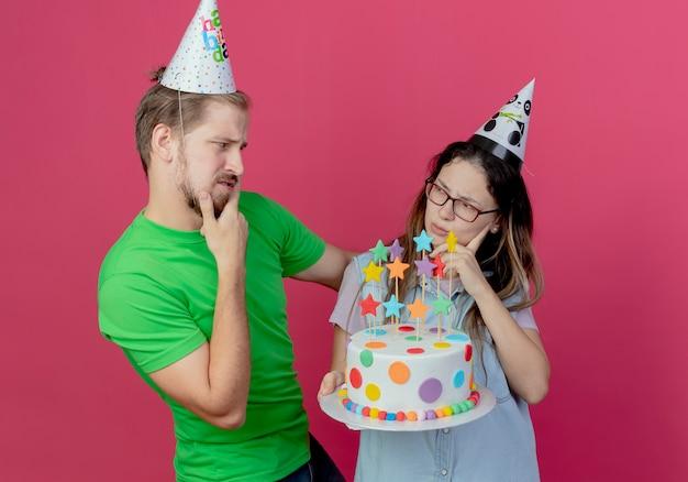 Casal jovem confuso com chapéu de festa se olha e a aniversariante segurando um bolo isolado na parede rosa