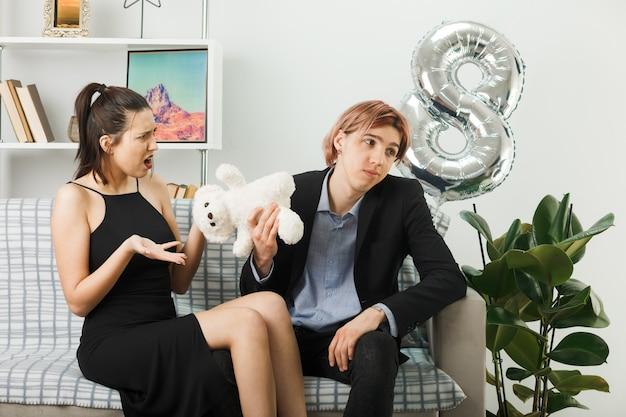 Casal jovem confuso no dia da mulher feliz com o ursinho de pelúcia sentado no sofá da sala de estar