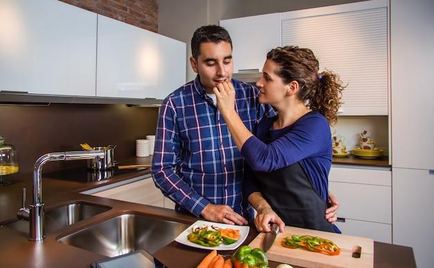 Casal jovem cortando vegetais na cozinha para preparar comida