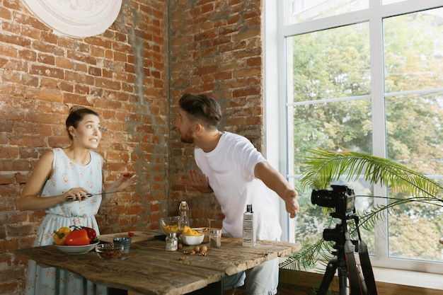 Casal jovem cozinhando e gravando vídeo ao vivo para vlog e redes sociais