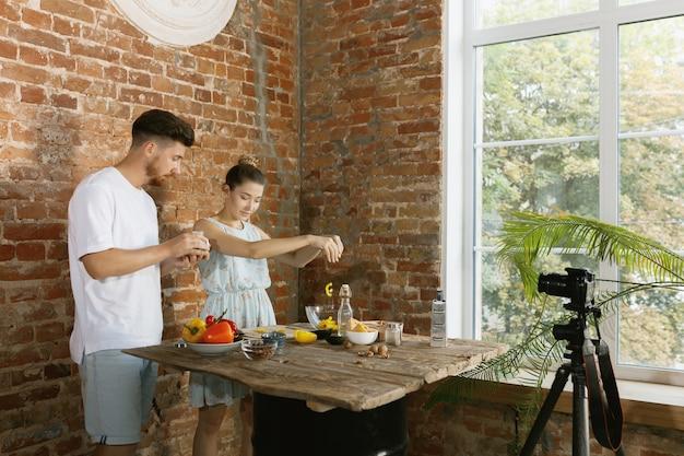 Casal jovem cozinhando junto e gravando vídeo ao vivo para vlog