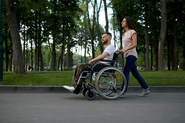 Casal jovem da família com cadeira de rodas, caminhando no parque. veterano paralítico e com deficiência, cuidar de um homem deficiente. marido e mulher superam dificuldades juntos, relacionamentos afetuosos