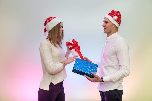 Casal jovem da moda comemorando o dia dos namorados dando presentes um ao outro