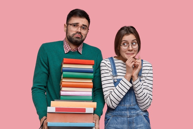 Casal jovem de alunos fica perto, segura uma pilha de livros, estuda juntos, prepara-se para o seminário
