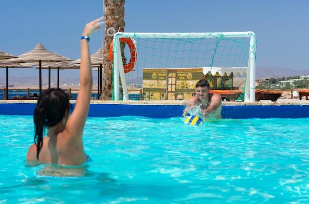 Casal jovem de atletas jogando pólo aquático no hotel em um dia ensolarado de verão