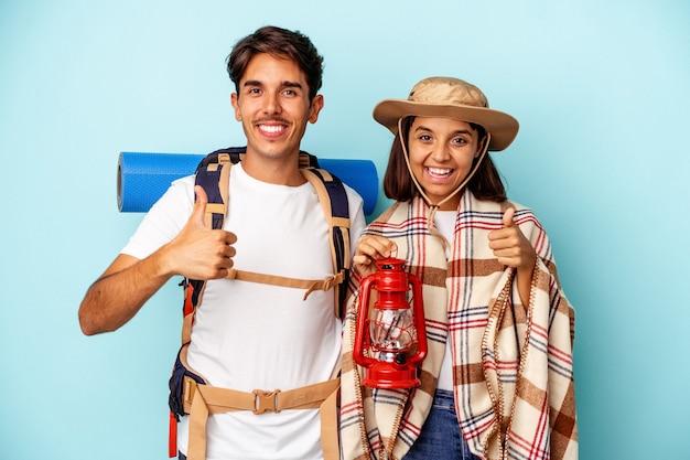 Casal jovem de caminhantes de raça mista isolado em fundo azul, sorrindo e levantando o polegar