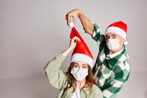 Casal jovem de chapéus de natal natal inverno divertido máscaras médicas no rosto