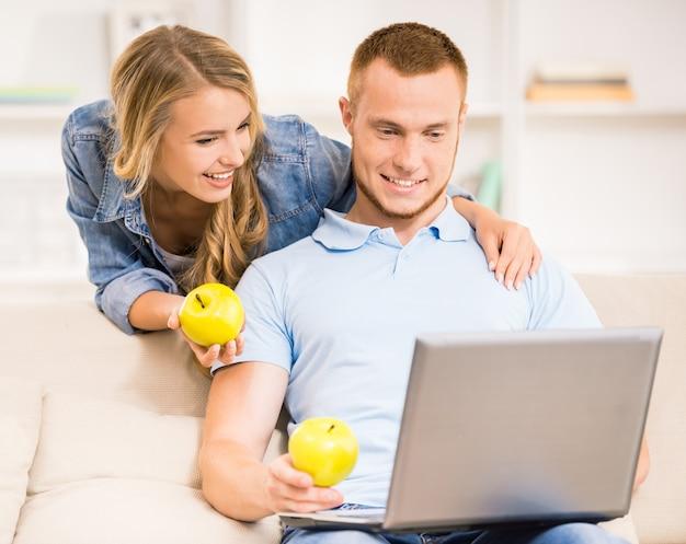 Casal jovem de família com maçãs verdes em casa.