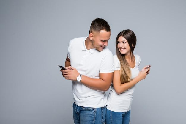 Casal jovem de homens e mulheres em pé com telefones celulares nas mãos, isolados em um fundo cinza