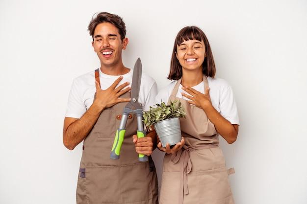 Casal jovem de jardineiro de raça mista, isolado no fundo branco, ri alto, mantendo a mão no peito.