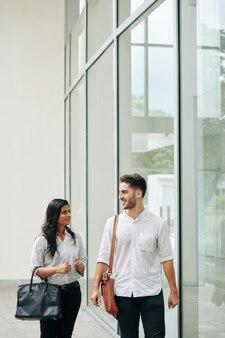 Casal jovem de negócios multiétnico sorridente, andando pela rua e discutindo notícias