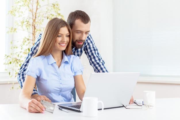 Casal jovem de negócios trabalhando com laptop no escritório