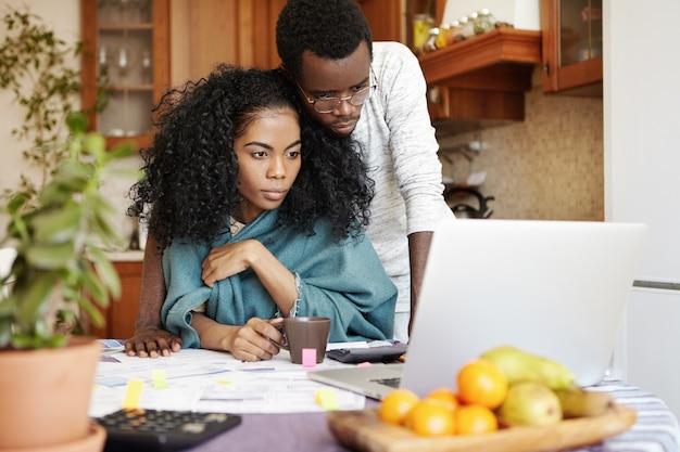 Casal jovem de pele escura usando laptop genérico enquanto gerencia o orçamento familiar