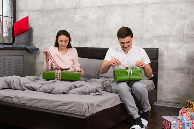 Casal jovem de pijama desempacotando seus presentes enquanto está sentado na cama no quarto em estilo loft na manhã de natal