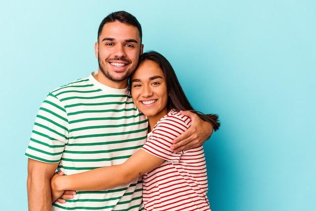Casal jovem de raça mista isolado em fundo azul