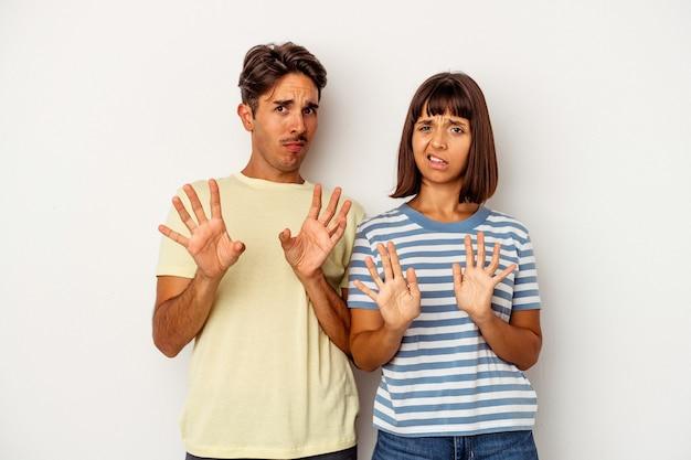 Casal jovem de raça mista, isolado no fundo branco, rejeitando alguém mostrando um gesto de nojo.