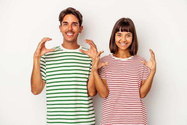 Casal jovem de raça mista, isolado no fundo branco, segurando algo com as palmas das mãos, oferecendo-se para a câmera.