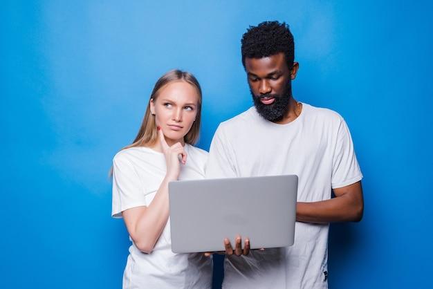 Casal jovem de raça mista segurando laptop isolado na parede azul