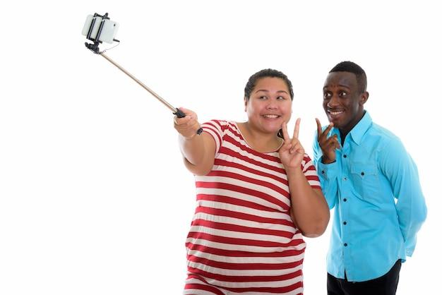 Casal jovem de raça mista usando bastão de selfie para tirar foto