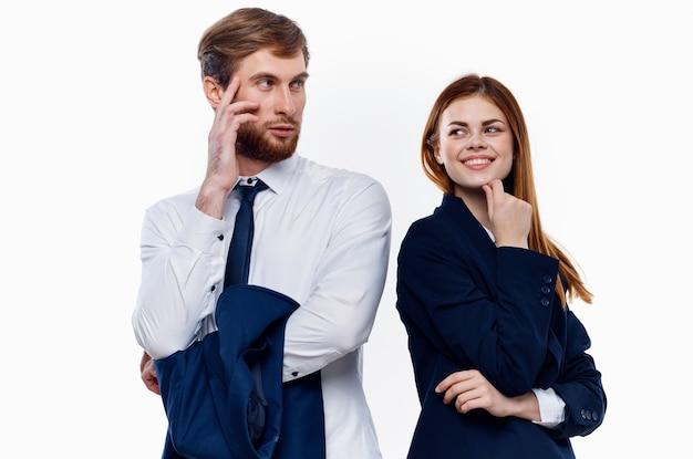 Casal jovem de terno fica ao lado de colegas de trabalho comunicando finanças